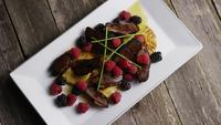 Rotating shot of a delicious smoked duck bacon dish with grilled pineapple, raspberries, blackberries, and honey - FOOD 089