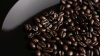 Rotating shot of delicious, roasted coffee beans on a white surface - COFFEE BEANS 013