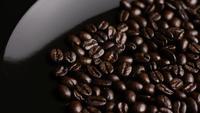 Foto giratoria de deliciosos granos de café tostados sobre una superficie blanca - CAFÉ HABAS 013