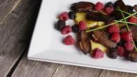 Rotating shot of a delicious smoked duck bacon dish with grilled pineapple, raspberries, blackberries, and honey - FOOD 121