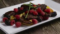 Rotating shot of a delicious smoked duck bacon dish with grilled pineapple, raspberries, blackberries, and honey - FOOD 099