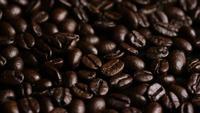 Foto giratoria de deliciosos granos de café tostados sobre una superficie blanca - CAFÉ HABAS 016