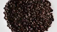 Foto giratoria de deliciosos granos de café tostados sobre una superficie blanca - CAFÉ HABAS 054