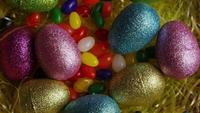 Rotating shot of Easter decorations and candy in colorful Easter grass - EASTER 016