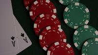 Rotating shot of poker cards and poker chips on a green felt surface - POKER 046