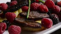 Rotating shot of a delicious smoked duck bacon dish with grilled pineapple, raspberries, blackberries, and honey - FOOD 103
