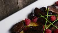 Rotating shot of a delicious smoked duck bacon dish with grilled pineapple, raspberries, blackberries, and honey - FOOD 112