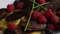 Rotating shot of a delicious smoked duck bacon dish with grilled pineapple, raspberries, blackberries, and honey - FOOD 097