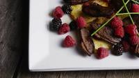 Rotating shot of a delicious smoked duck bacon dish with grilled pineapple, raspberries, blackberries, and honey - FOOD 110