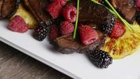Rotating shot of a delicious smoked duck bacon dish with grilled pineapple, raspberries, blackberries, and honey - FOOD 120