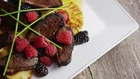 Rotating shot of a delicious smoked duck bacon dish with grilled pineapple, raspberries, blackberries, and honey - FOOD 109
