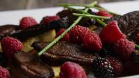 Foto giratoria de un delicioso plato de tocino de pato ahumado con piña a la parrilla, frambuesas, moras y miel - FOOD 104