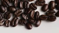 Foto giratoria de deliciosos granos de café tostados sobre una superficie blanca - CAFÉ HABAS 033