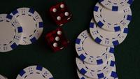 Rotating shot of poker cards and poker chips on a green felt surface - POKER 033
