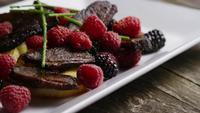 Rotating shot of a delicious smoked duck bacon dish with grilled pineapple, raspberries, blackberries, and honey - FOOD 101