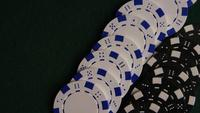 Rotating shot of poker cards and poker chips on a green felt surface - POKER 060
