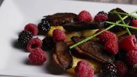 Drehender Schuss eines köstlichen geräucherten Entenspeckgerichtes mit gegrillter Ananas, Himbeeren, Brombeeren und Honig - FOOD 115