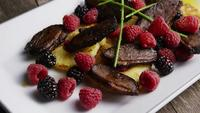 Rotating shot of a delicious smoked duck bacon dish with grilled pineapple, raspberries, blackberries, and honey - FOOD 116