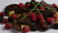 Rotating shot of a delicious smoked duck bacon dish with grilled pineapple, raspberries, blackberries, and honey - FOOD 096
