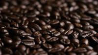 Foto giratoria de deliciosos granos de café tostados sobre una superficie blanca - CAFÉ HABAS 023