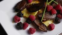 Rotating shot of a delicious smoked duck bacon dish with grilled pineapple, raspberries, blackberries, and honey - FOOD 111
