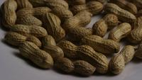 Cinematic, rotating shot of peanuts on a white surface - PEANUTS 009