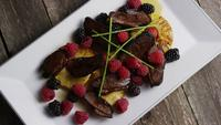 Rotating shot of a delicious smoked duck bacon dish with grilled pineapple, raspberries, blackberries, and honey - FOOD 091