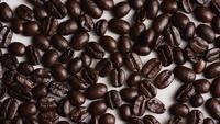 Foto giratoria de deliciosos granos de café tostados sobre una superficie blanca - CAFÉ HABAS 030