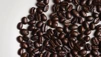 Foto giratoria de deliciosos granos de café tostados sobre una superficie blanca - CAFÉ HABAS 028