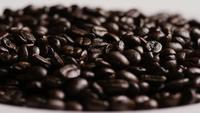 Rotating shot of delicious, roasted coffee beans on a white surface - COFFEE BEANS 076