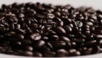 Foto giratoria de deliciosos granos de café tostados sobre una superficie blanca - CAFÉ HABAS 076