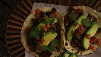 Rotating shot of delicious tacos on a wooden surface - BBQ 130