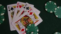 Rotating shot of poker cards and poker chips on a green felt surface - POKER 010