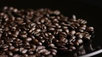 Rotating shot of delicious, roasted coffee beans on a white surface - COFFEE BEANS 022