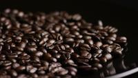 Foto giratoria de deliciosos granos de café tostados sobre una superficie blanca - CAFÉ HABAS 022