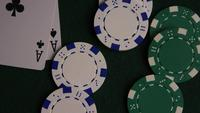 Rotating shot of poker cards and poker chips on a green felt surface - POKER 044