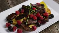 Rotating shot of a delicious smoked duck bacon dish with grilled pineapple, raspberries, blackberries, and honey - FOOD 095