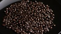 Rotating shot of delicious, roasted coffee beans on a white surface - COFFEE BEANS 011