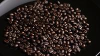 Foto giratoria de deliciosos granos de café tostados sobre una superficie blanca - CAFÉ HABAS 011
