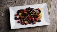 Rotating shot of a delicious smoked duck bacon dish with grilled pineapple, raspberries, blackberries, and honey - FOOD 090