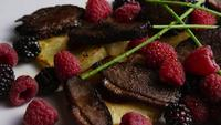 Rotating shot of a delicious smoked duck bacon dish with grilled pineapple, raspberries, blackberries, and honey - FOOD 117