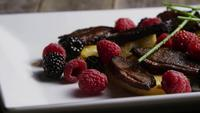 Rotating shot of a delicious smoked duck bacon dish with grilled pineapple, raspberries, blackberries, and honey - FOOD 100