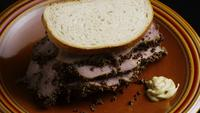 Rotating shot of delicious, premium pastrami sandwich next to a dollop of dijon mustard - FOOD 045