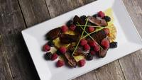Rotating shot of a delicious smoked duck bacon dish with grilled pineapple, raspberries, blackberries, and honey - FOOD 088