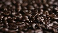 Rotating shot of delicious, roasted coffee beans on a white surface - COFFEE BEANS 051