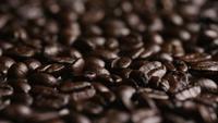 Foto giratoria de deliciosos granos de café tostados sobre una superficie blanca - CAFÉ HABAS 051