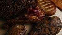 Rotating shot of a variety of delicious, premium smoked meats on a wooden cutting board - FOOD 072