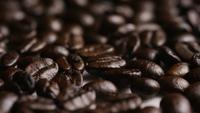Foto giratoria de deliciosos granos de café tostados sobre una superficie blanca - CAFÉ HABAS 053