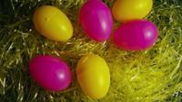 Drehender Schuss von Ostern-Dekorationen und von Süßigkeit im bunten Ostern-Gras - OSTERN 001