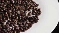Foto giratoria de deliciosos granos de café tostados sobre una superficie blanca - CAFÉ HABOS 038